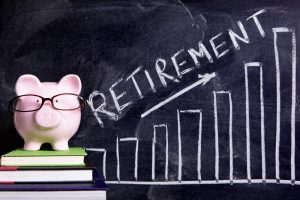 Pink piggy bank with glasses standing on books next to a blackboard with retirement savings message on blackboard