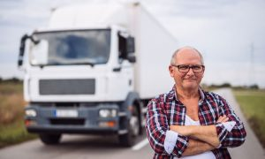 Trucker standing in front of his white OTR truck